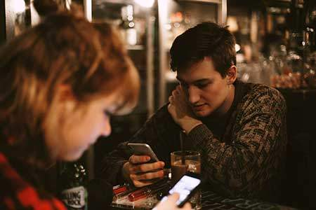 man and woman looking at cellphones